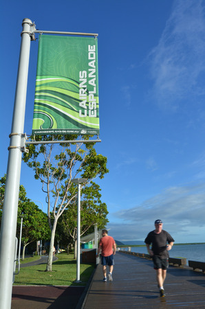 cairns: CAIRNS, AUS - APR 15 2016:Men runs on Cairns Esplanade, a very popular tourist travel destination in Cairns Queensland, Australia.