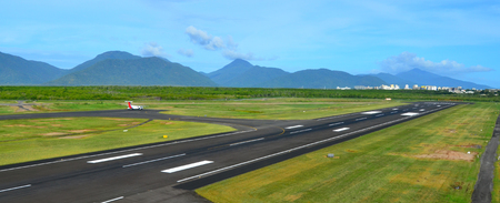cns: CAIRNS, AUS - APR 23 2016:Cairns Airport runway in Queensland Australia.The airport is located 7 kilometres (4.3 mi) north of the Cairns central business district, in the suburb of Aeroglen.