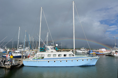 cairns: CAIRNS, AUS - APR 15 2016:Rainbow over Cairns Marlin Marina in Queensland Australia.  Located at the entrance to Trinity Inlet its a significant departure location of tourism tours to the Great Barrier Reef.