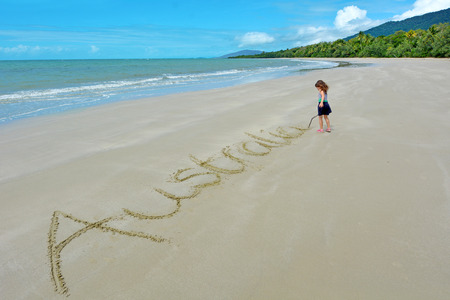 tribulation: Little girl write the word Australia in the seashore sand of Cape Tribulation at Daintree National Park in the tropical north of Queensland, Australia Stock Photo