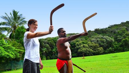 australian ethnicity: Yirrganydji Aboriginal warrior teaches a young woman how to throw a boomerang during cultural show in Queensland, Australia.