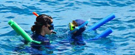 snorkelling: Woman instructor teach little girl how to snorkelling dive in the Great Barrier Reef Queensland Australia