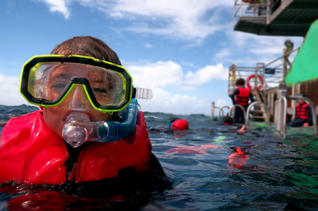 barrier: Little girl (age 5-6) prepare to  snorkeling dive in the Great Barrier Reef Queensland Australia Stock Photo