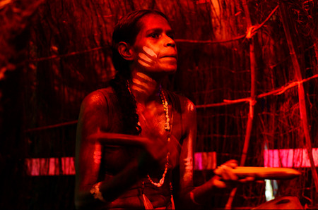 australian ethnicity: Yirrganydji Aboriginal woman play Aboriginal music with Clapstick, percussion musical Instrument made out of wood, during Aboriginal culture show in Queensland, Australia. Stock Photo