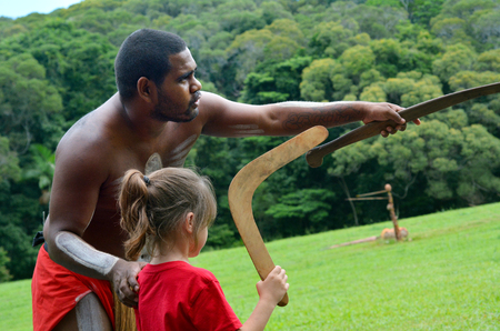 australian ethnicity: Yirrganydji Aboriginal warrior teaches a little girl how to throw a boomerang during cultural show in Queensland, Australia. Stock Photo