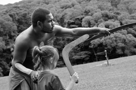 australian ethnicity: Yirrganydji Aboriginal warrior teaches a little girl how to throw a boomerang during cultural show in Queensland, Australia.(BW)