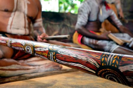 australian ethnicity: Yirrganydji Aboriginal men play Aboriginal music on didgeridoo and wooden instrument during Aboriginal culture show in Queensland, Australia.