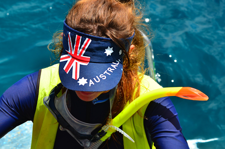 femal: Australian woman get ready to dive in the great barrier reef in Queensland, Australia, a popular tourist destination of 2 million visitors every year.