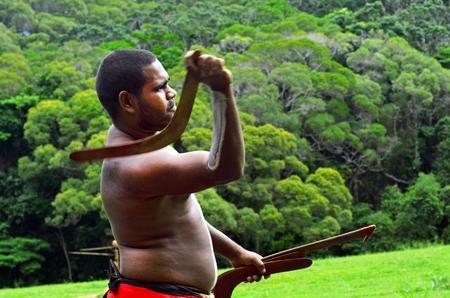 australian ethnicity: Yirrganydji Aboriginal warrior throw boomerang during cultural show in Queensland, Australia.