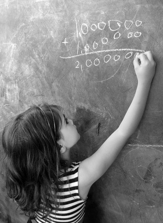 additional training: Smart child (girl age 5-6) calculat and solve hard mathematic equation on a cluck board in school. Education cocept with copy space text Stock Photo