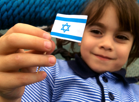 fertility emblem: Israeli child (girl age 5-6) holds small Israel flag during Israels independents day. Stock Photo