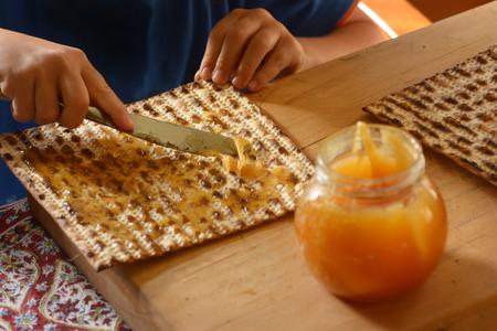 pesakh: Jewish child hands spread honey on Matzo bread during Passover Jewish holiday.
