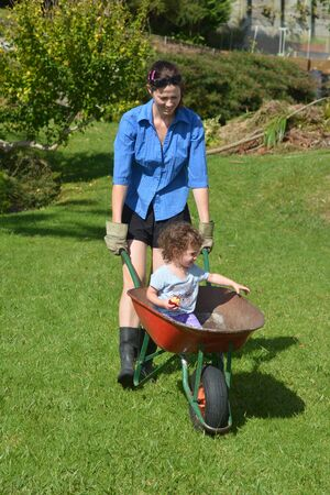 helps: Young woman  (age 30-35) carry her daughter (1-2) in a wheelbarrow during gardening work in the garden