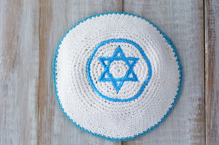kippah: Flat lay of a Knitted kippah with embroidered blue and white Star of David on a wooden table. Jewish lifestyle concept copy space Stock Photo