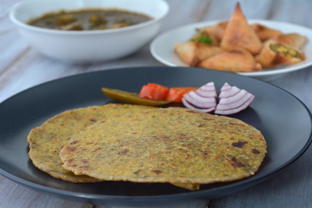 punjabi: Paratha flatbread Indian cuisine served with traditional Punjabi Palak Paneer dish and Samosa.India food background and texture copy space