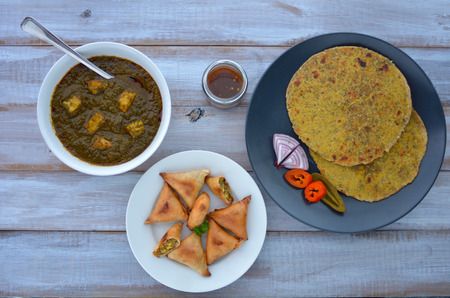 punjabi: Flat lay of Paratha flatbread Indian cuisine served with traditional Punjabi Palak Paneer dish and Samosa.India food background and texture copy space