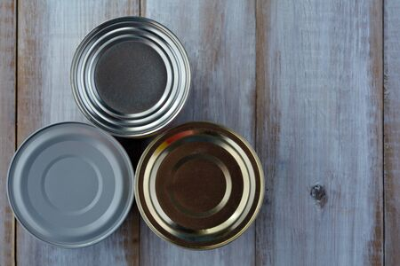 tinned goods: Flat lay of three tin cans in a shape of a pyramid.Food background and texture with copy space