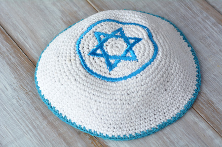 kippa: Knitted kippah with embroidered blue and white Star of David on a wooden table. Jewish lifestyle concept copy space