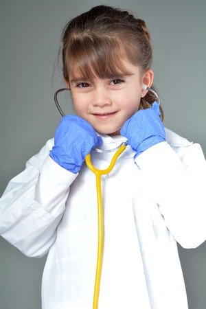 pretend: Little child (girl age 6) who wants to be a physician play pretend to be medical doctor in ambulatory care clinic looks at the camera.Medical concept with copy space.