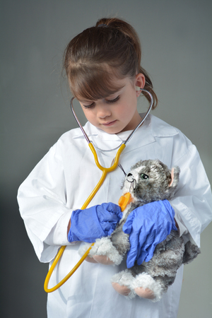 pretend: Little child (girl age 6) who wants to be a veterinarian play pretend to be an animal doctor in veterinary clinic. Medical concept with copy space Stock Photo