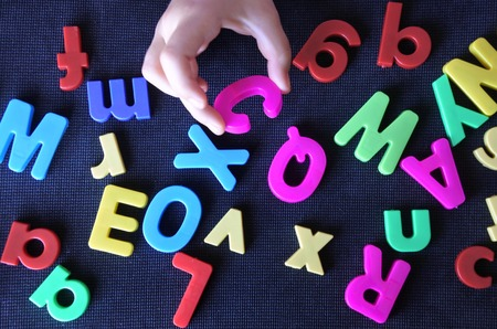 early childhood education: Flat lay view of a hand of a little child learns the english language alphabet letters. Early childhood education concept . copy space Stock Photo