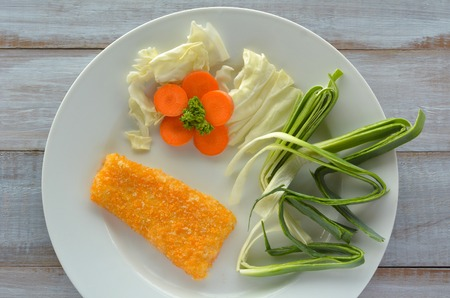 crumbing: Flat lay of Crumbed fish fillet served on a plate with vegetables. Pescetarian diet concept. Food background and texture . copy space