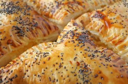 Extream Close up of Triangular Burekas - a puff pastry pie with cheese coated with sesame seeds. Food background and texture Burekas.