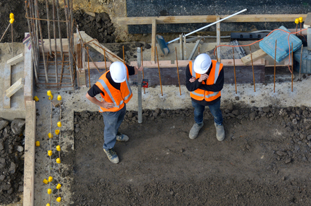 Aerial view of two unrecognised civil engineers inspecting the work progress in a construction site. Building development concept with copy space