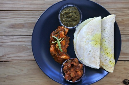 masala dosa: Flat lay of Indian food,  Chicken Curry served with Masala Dosa with Sambar and Channa Masala. Food background and texture. copy space