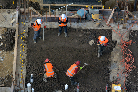 Aerial to view of construction site workers leveling cement in building site Stock Photo