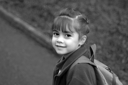 road shoulder: Happy little girl (age 6) with school bag walks to school, looking back over her shoulder at the camera . Education concept. copy space