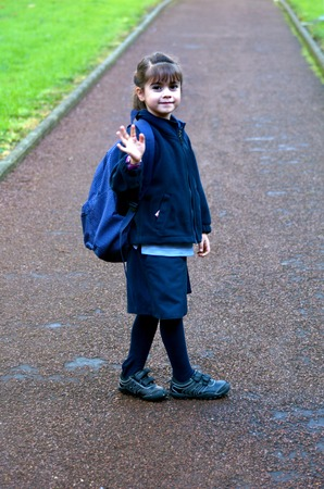 Little girl (age 6) with school bag waves goodbye.  Education concept. Stock Photo