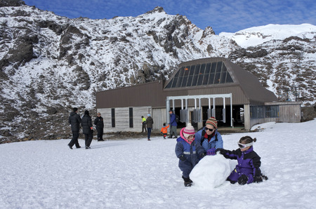 NATIONAL PARK, NZL - JULY 12 2016:Visitors builds a snowman in Whakapapa skifield on Mount Ruapehu in Tongariro National Park in the centre of New Zealands North Island