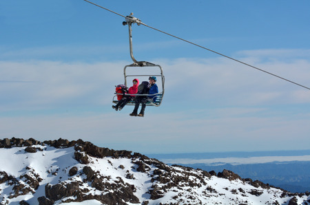 north island: NATIONAL PARK, NZL - JULY 12 2016:Couple travel on Ski lift to the top of Mount Ruapehu in Tongariro National Park in the centre of New Zealands North Island
