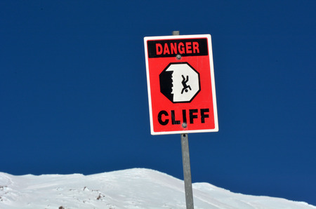 steep cliff sign: Danger steep cliff sign on snow cape mountain summit background. Stock Photo