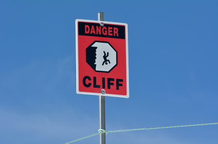 steep cliff sign: Danger steep cliff sign against blue sky background. Stock Photo