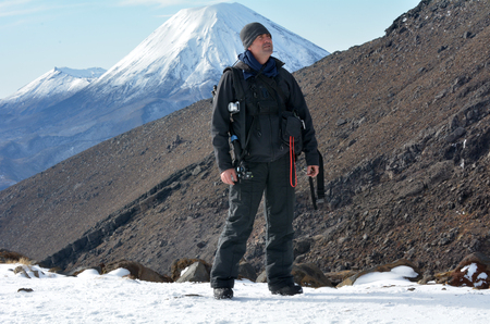 north island: Travel photographer hike the Tongariro crossing with Mount Ngauruhoe  and Mount Tongariro at the background in Tongariro National Park at the centre of New Zealands North Island
