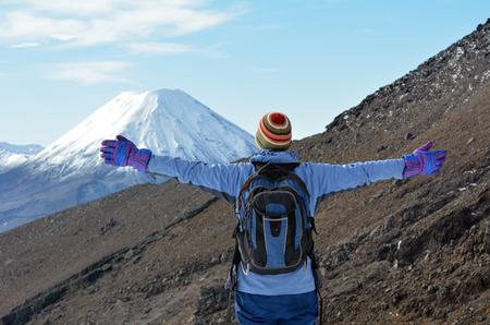 Woman (back view) hike the Tongariro crossing with Mount Ngauruhoe  and Mount Tongariro at the background in Tongariro National Park at the centre of New Zealands North Island