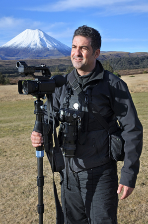 documenting: Professional nature, wildlife and travel videographerphotographer photographing Mount Ngauruhoe outdoors during on location photo assignment in Tongariro National Park New Zealand. copy space.