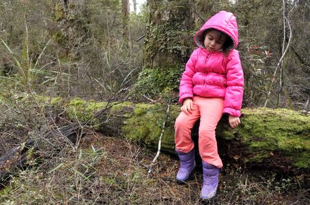 winter escape: Little girl (age 6) sit on a tree log with sad face expression,  lost in a rain forest. Travel concept. copy space