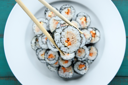 Close up of chopsticks holds sushi maki gunkan roll over a plate or platter set. Served  in Japanese bar restaurant. Top view, flat lay. Food background. copy space