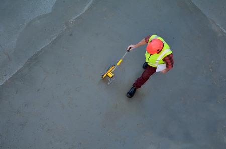 Luchtmening van een voormanbouwer die concrete vloer met een rollende meetlint in een bouwwerf meten. Ruimte kopiëren