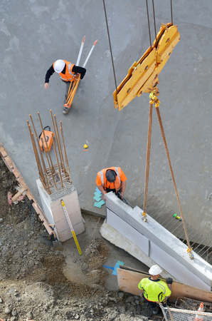 Unrecognizable construction workers guides a structural precast concrete into place as a crane lowers it onto a building floor.
