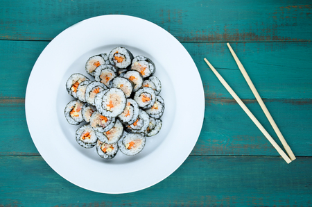 roll bar: Sushi maki gunkan roll plate or platter set. Served with chopsticks, on a wooden planks background in Japanese bar restaurant. Top view, flat lay. Food background. copy space