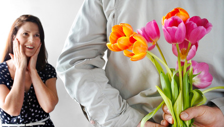 hesitant: Hesitant woman (age 30-35) receive tulip flowers from her lover. Couple relationship concept. Stock Photo