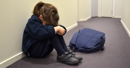 bully: One young elementary school girl (age 5-6)  wearing school uniform and backpack sitting on a corridor floor,  cry in a corridor.Childhood concept. copy space