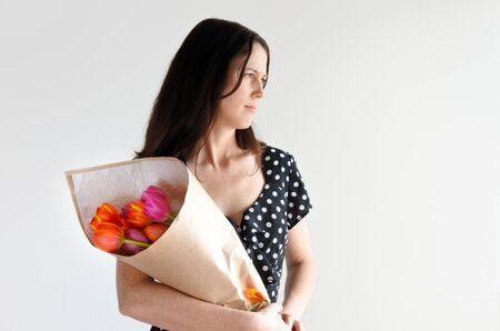 Unsure Frau (Alter 30-35) erhalten Tulpenblumen von ihrem Geliebten. Paar-Beziehungskonzept. Platz kopieren Standard-Bild