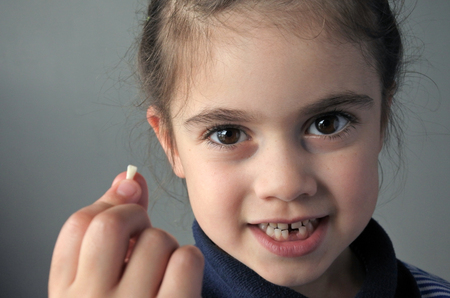 Proud young girl (age 6) holds her first falling milk teeth, looks at the camera. Childhood healthcare concept.real people copy space Stock fotó