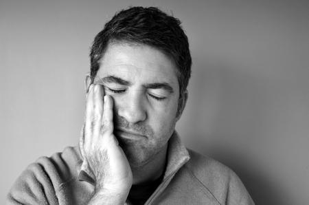 Retrato de un hombre triste (edad 40-45) sostiene su mano sobre su rostro en el dolor. Concepto de la crisis de mediana edad. personas reales espacio de la copia (BW)