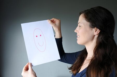 dissimulation: Young woman looks at a drawing with a happy face. Woman lifestyle concept. copy space Stock Photo